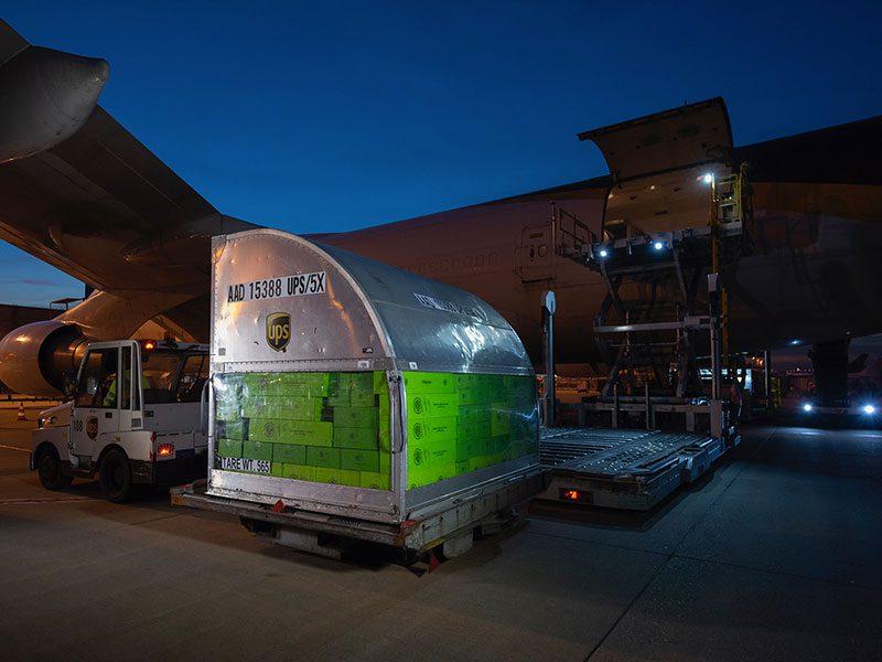 Flugzeug Frachtcontainer mit beadenen KUKKO Paketen vor Flugzeug